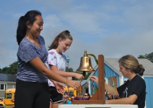 Students sign the logbook and ring the ship's bell